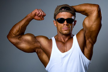 A strong man in sunglasses shows his muscles