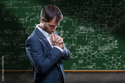 Scientist in front of chalk board in deep thought