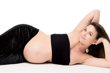 Donna incinta sdraiata su sfondo bianco