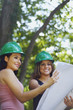 Hispanic architects in green hard hats viewing blueprints outdoors