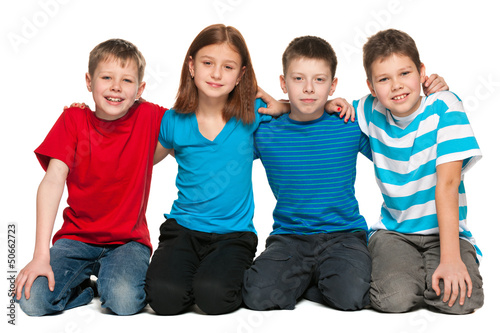 Four children are sitting on the floor