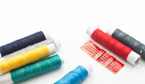 sewing needle with colorful thread spools background
