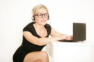 Frau mit Headset am Laptop