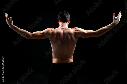 handsome muscleman against dark background