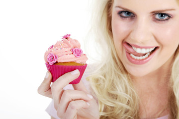 Junge hübsche Frau mit Cupcake leckt Mund