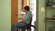 Man in a wheelchair entering his home