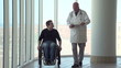 Man in wheelchair walking with doctor