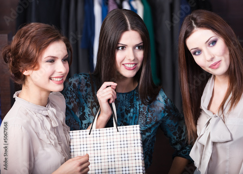 Three girls buy dresses in the store