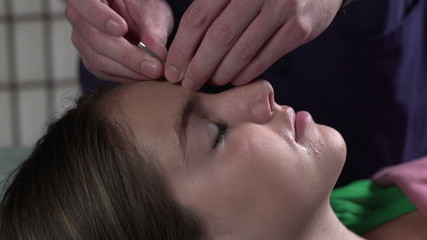 Woman having Acupuncture done on her face