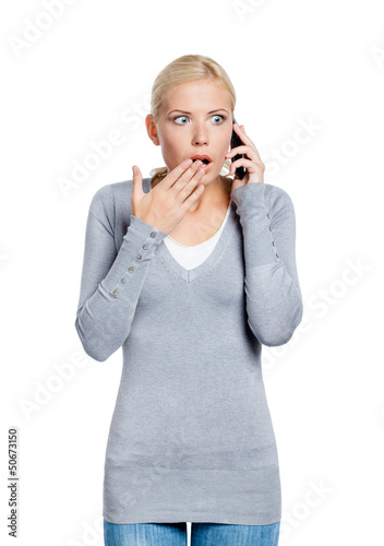 Speaking on phone shocked woman covers her mouth with hand