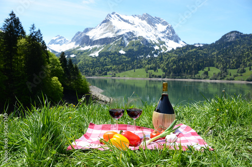 Wine and vegetables served at a picnic in Alpine meadow. Switzer