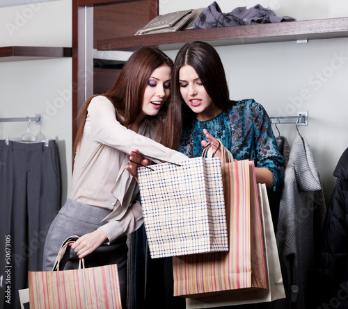Two girlfriends buy clothes at cut rates in the store