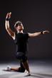 Dancer dancing dances in dark studio