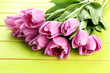 Beautiful bouquet of purple tulips on green wooden background