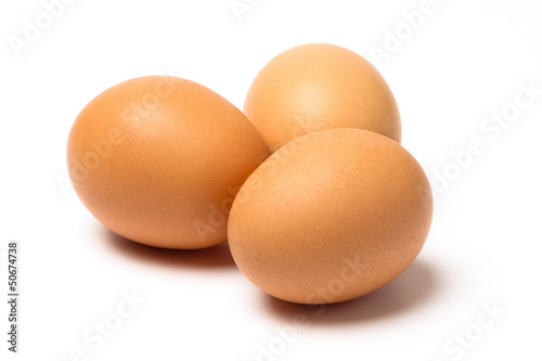 Three brown eggs with shadow isolated on a white background