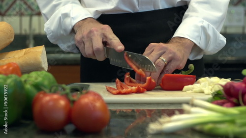 Man cutting red peppers in the kitchen, dolly shot