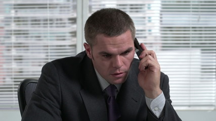 Business man on the phone angry at his desk
