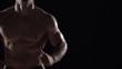 Muscular man running towards camera, torso shot left