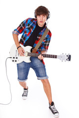Young man is playing on electric guitar