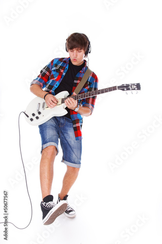Teenage boy is playng on guitar very passionately