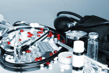 Medicines and stethoscope in grey light