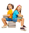Two girls sitting on books