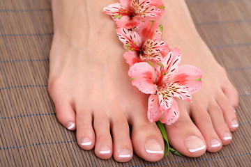 Beautiful woman legs with pedicure on bamboo mat