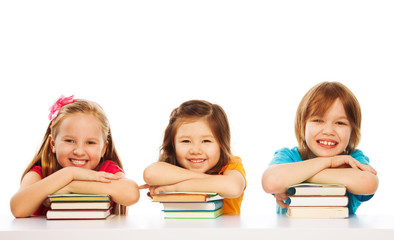 Three smart kids on pile of books