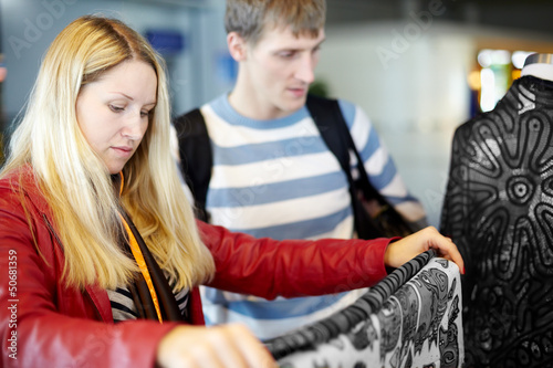 Young woman in jacket and man considers colorful fabric