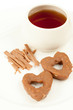 Two cookies in shape of heart, cup with tea and cinnamon sticks