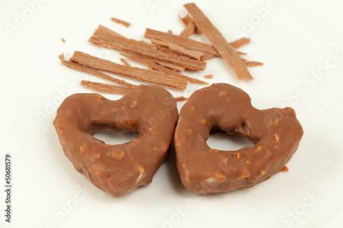 Cookies shaped as heart and sticks of cinnamon on plate