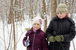 Boy and his younger sister stand in winter park with ski poles