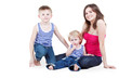 Mother and two sons in striped singlets sit on floor