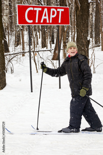 Smiling boy on skis at sign start at start point of ski race