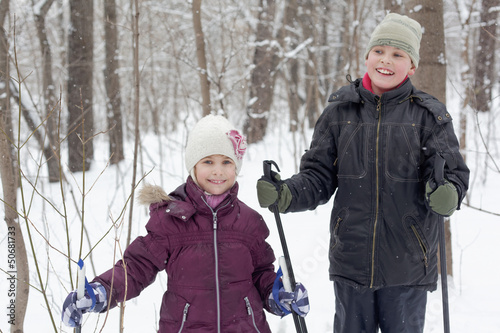 Smiling boy and his younger sister stand in winter park with ski