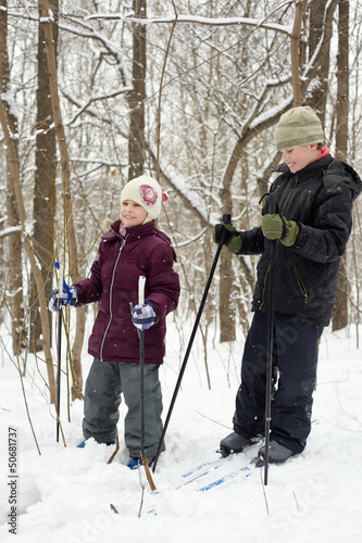Smiling boy and his younger sister ski in winter park