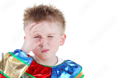 Little boy in carnival suit looks through ring made of thumb