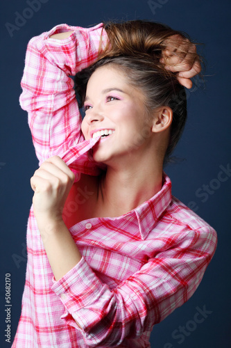 Beautiful pretty girl in pink plaid shirt holds hair