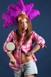 Singing girl in pink shirt in hat with feathers with small drum