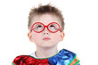 Little boy in big red glasses and clown costume looks up