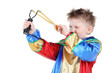 Little boy in clown costume holds slingshot and aims isolated