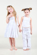 Two little funny and serious girl in white clothes stand