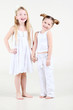 Two little funny and laughing girl in white clothes stand