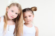 Two little funny and serious girl in white clothes look