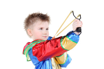 Boy in clown costume holds slingshot and aims up isolated