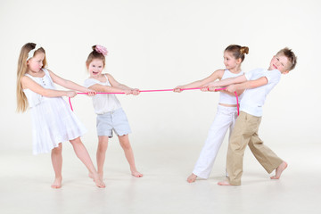 Four cute little boys and girls overtighten pink rope