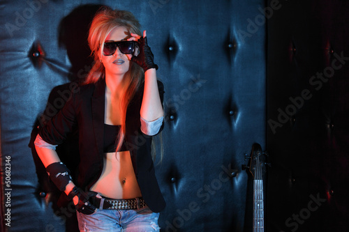 Young woman rocker in big sunglasses stands near wall