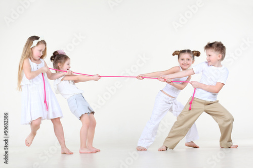 Four happy little boy and girls in white overtighten pink rope.