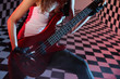 Part of body of girl playing red electric guitar in studio