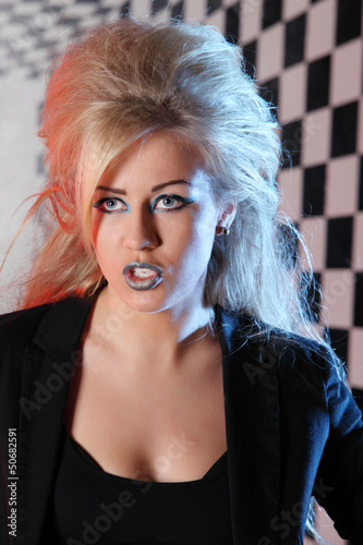 Young woman with unusual hairdo and makeup sings in studio